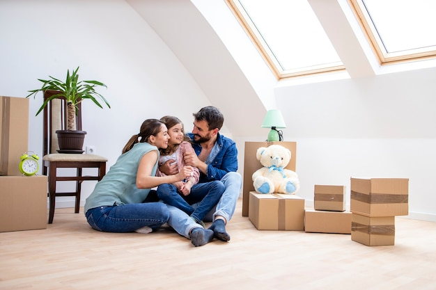 Happy family with daughter sitting on the parquet floor and celebrating moving into new house real estate