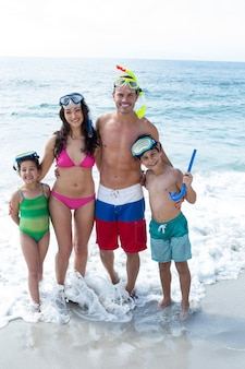 Happy family with diving goggles at beach