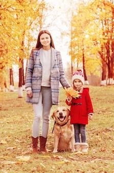 Счастливая семья с собакой в солнечном осеннем парке