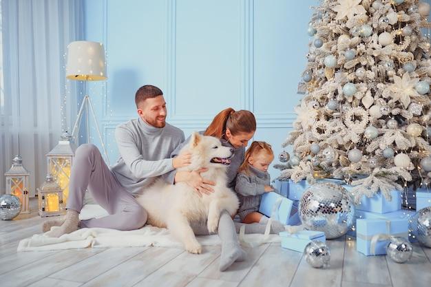 Happy family with dog near by christmas tree.
