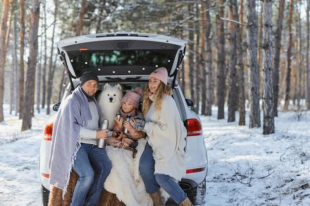 Счастливая семья с собакой в отпуске во время зимних каникул возле дороги. одетый в теплую одежду сидит на багажнике машины и пьет чай из термоса. место для текста. зимние каникулы