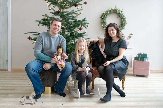 Happy family with dog smiling and looking at camera in room with cristmas tree and new year decorations