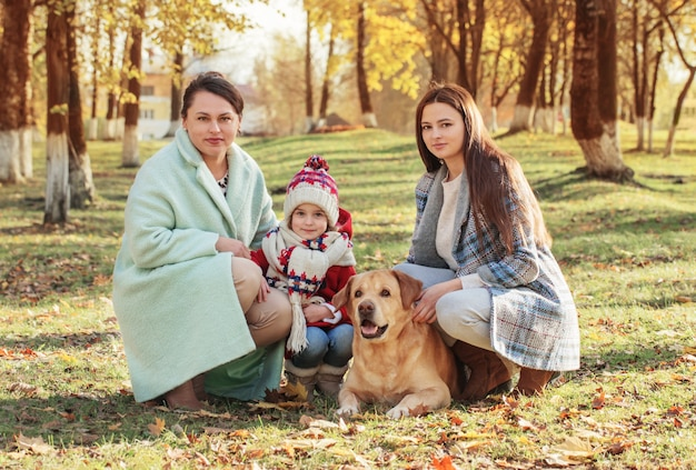 Happy family with dog in sunny autumn park