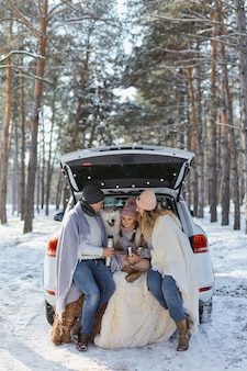 Happy family with dog on vacation during the winter holidays near road. dressed in warm clothes sitting on the trunk of a car and drinking tea from a thermos. space for text. winter vacation