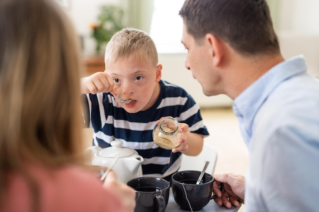 A happy family with down syndrome son at the table, having breakfast.