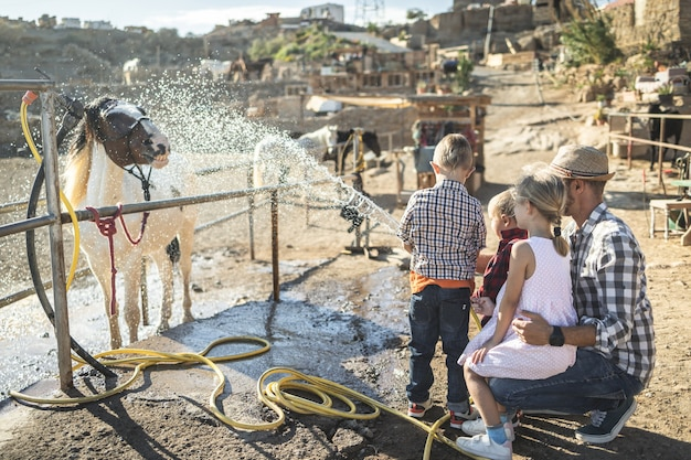 Happy family with father and children washing their horse outdoor at ranch farm