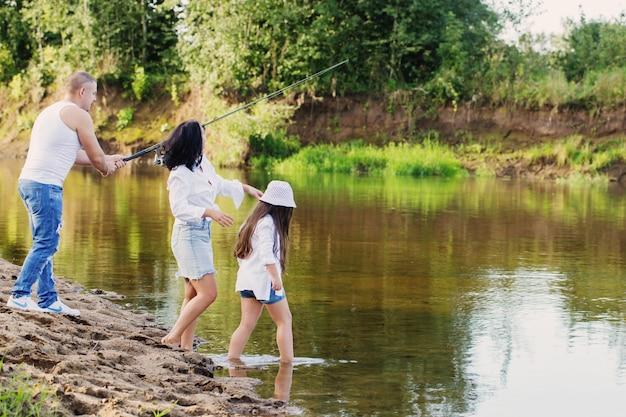 Счастливая семья с удочкой на летней реке