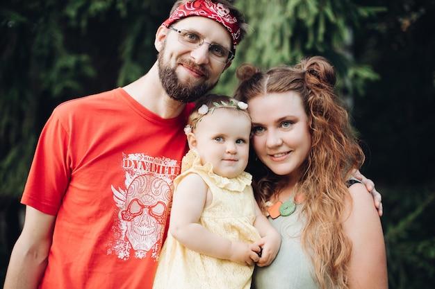 녹색 나무 배경에서 야외에서 함께 포즈를 취하고 웃고 있는 소녀와 함께 행복한 가족입니다. 부모가 되는 것을 즐기는 아이들을 안고 웃는 엄마와 아빠