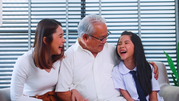Happy family with grandfather, mother and little daughter spending time together in living room.