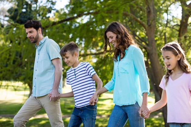 公園を歩いて手をつないで幸せな家族