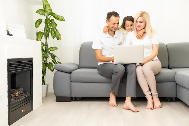 ソファに座ってラップトップを一緒に楽しんでいる子供の女の子と幸せな家族、面白いインターネットビデオを見て、オンライン電話をかけるコンピュータで家でリラックスして笑っている両親と子供の娘