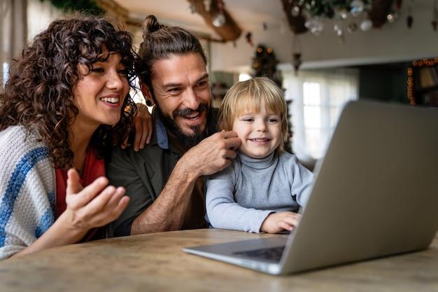 Счастливая семья с ребенком, весело проводящим время, используя ноутбук вместе, просматривая интернет-видео, делая онлайн-звонки дома