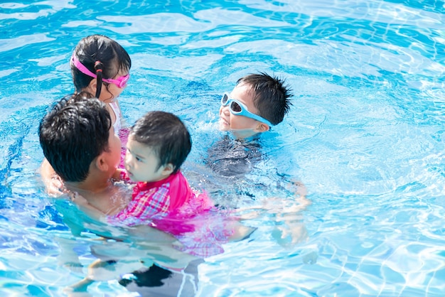 Happy family with kids having fun in swimming pool.