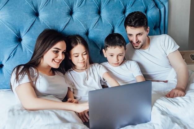 子供と幸せな家族はベッドに横たわって、ラップトップで何かを見ています。笑って楽しいです。