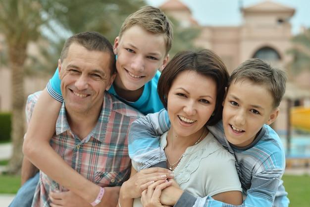 Счастливая семья с детьми возле бассейна на летних каникулах