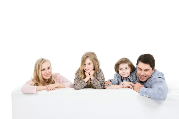 Счастливая семья с детьми на диване на белом фоне