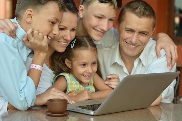 テーブルでラップトップと幸せな家族