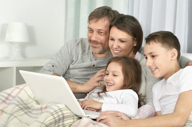 部屋にラップトップを持つ幸せな家族