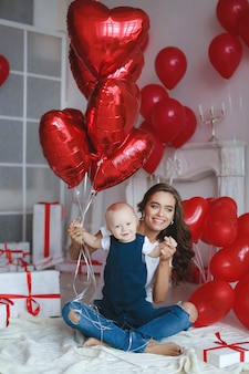 Happy family with little baby boys in festive atmosphere on background of balloons and gift boxes