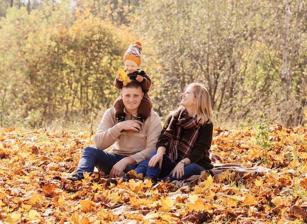 Счастливая семья с маленьким ребенком в осеннем парке
