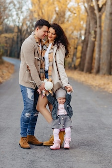 Happy family with little baby walk at park road with yellow trees at autumn