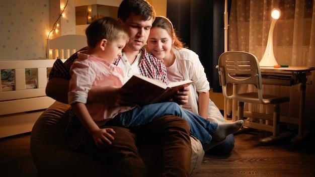 Счастливая семья с маленьким мальчиком, читающим книгу ночью перед сном. концепция воспитания детей и семьи, проводящей время вместе в ночное время.