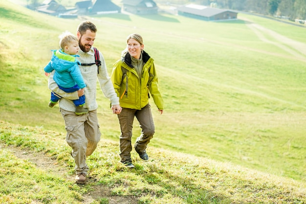 Happy family with little child doing trekking on switzerland mountain in summer time