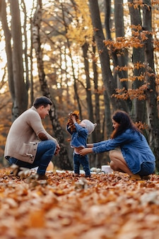 Happy family with little cute child in park on yellow leaf with big pumpkin in autumn