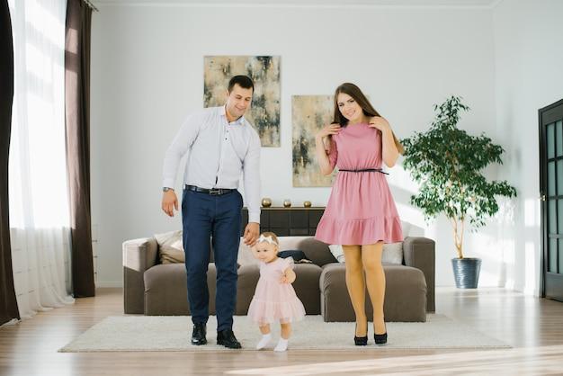 Счастливая семья с маленькой дочкой весело проводят время в своей квартире