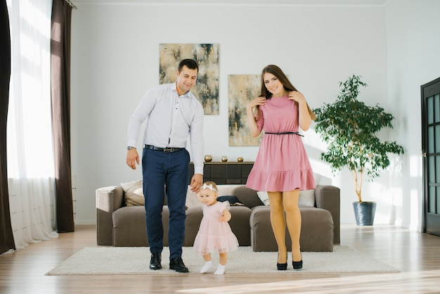 Happy family with little daughter have fun spending their free time in their apartment