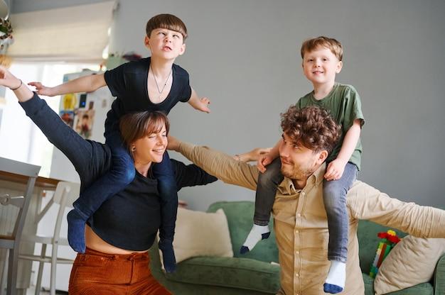 Счастливая семья с маленьким сыном весело дома. улыбающиеся родители и дети дошкольного возраста веселятся вместе, семья наслаждается свободным временем