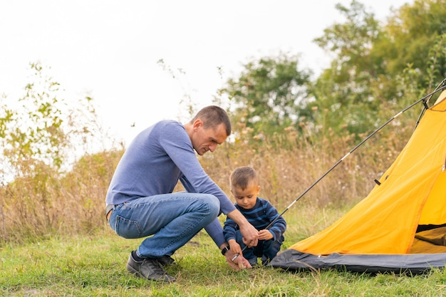Happy family with little son set up camping tent. happy childhood, camping trip with parents. a child helps to set up a tent