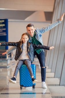 Happy family with luggage and boarding pass at airport waiting for boarding