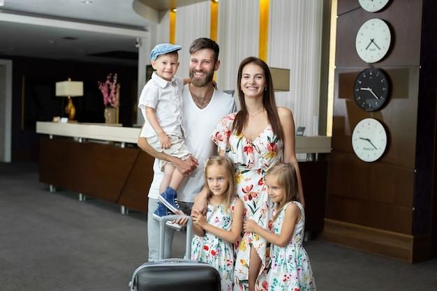호텔 리셉션 데스크 근처에 수하물이있는 행복한 가족.