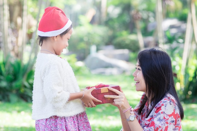 Happy family with mother and daughter holding christmas gift,x-mas concept