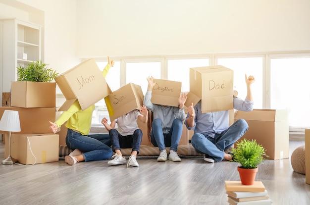 彼らの新しい家で楽しんでいる移動ボックスを持つ幸せな家族