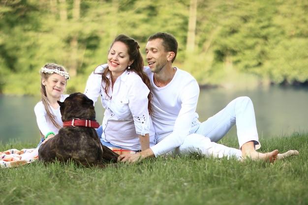 화창한 여름 날에 피크닉에 애완 동물 강아지와 함께 행복 한 가족. 임신 프리미엄 사진