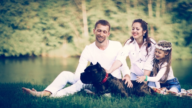 Happy family with pet dog at picnic in a sunny summer day. pregn