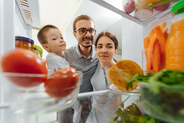Счастливая семья с продуктами возле холодильника на кухне. концепция счастливой семьи. здоровое питание