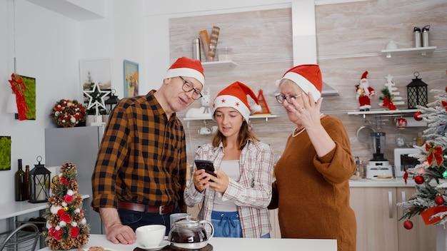 電話を使用してオンラインビデオ通話会議中にリモートの友人に挨拶するサンタ帽子を持つ幸せな家族