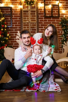 A happy family with a small child stands near a christmas tree with toys and gifts. happy childhood. new year's festive atmosphere. family relationship concept