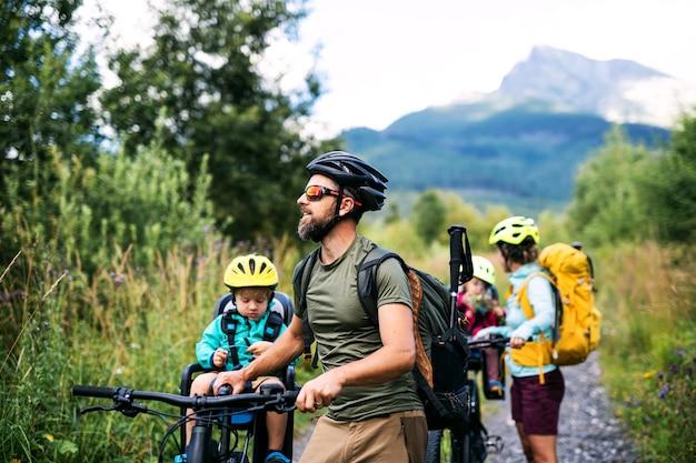夏の自然の中で屋外で自転車を持っている小さな子供たちと幸せな家族、スロバキアのハイタトラ。