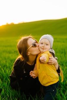 屋外で息子と幸せな家族。若い親は夏のフィールドで子供と一緒に歩く