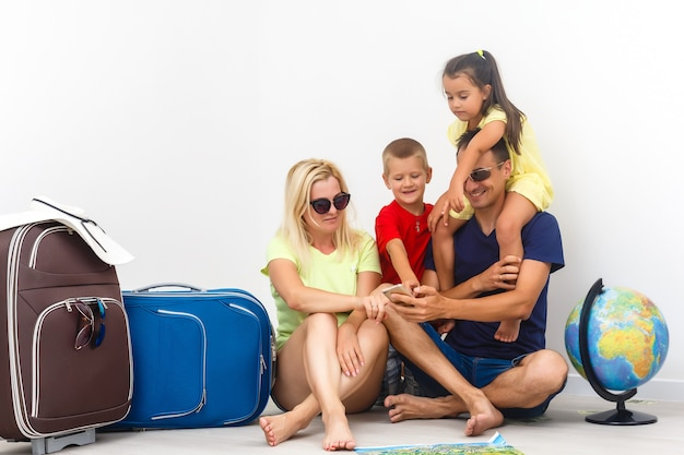 Happy family with suitcases near empty wall
