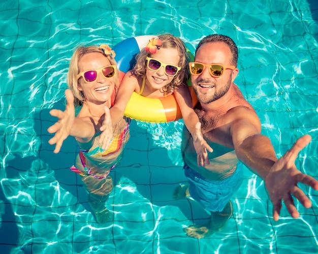 Счастливая семья с солнечными очками и цветами на волосах с красочной надувной в бассейне