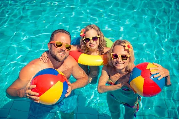 プールでカラフルなインフレータブルと彼らの髪にサングラスと花を持つ幸せな家族