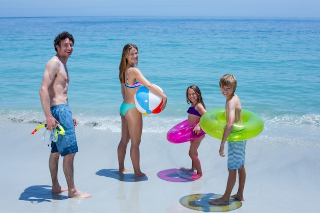 Happy family with swimming equipment at sea shore