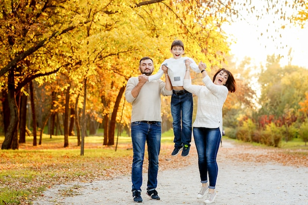 Happy family with teenage son outing in autumn park Premium Photo