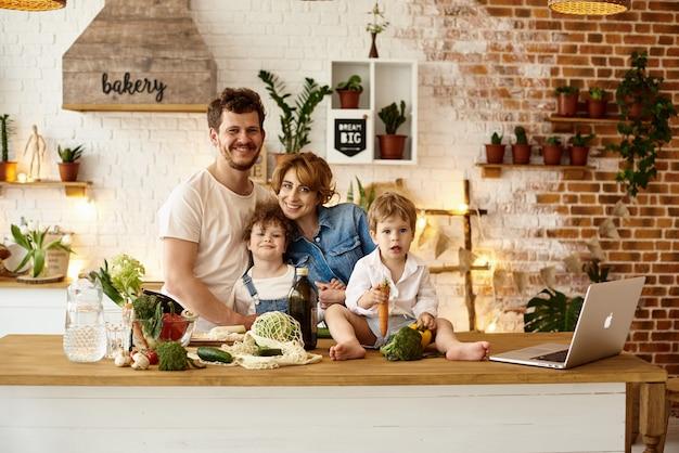 Счастливая семья с детьми готовит на кухне