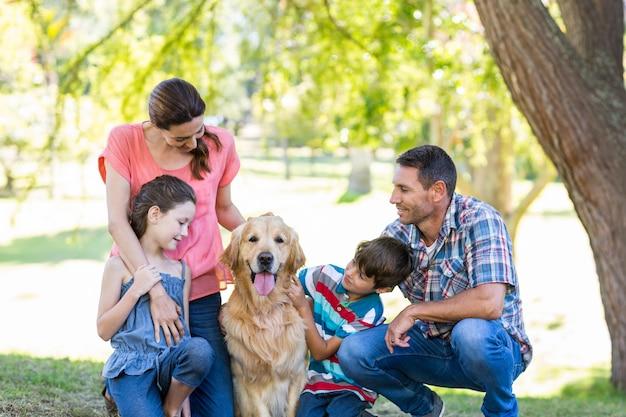 公園に犬がいる幸せな家族